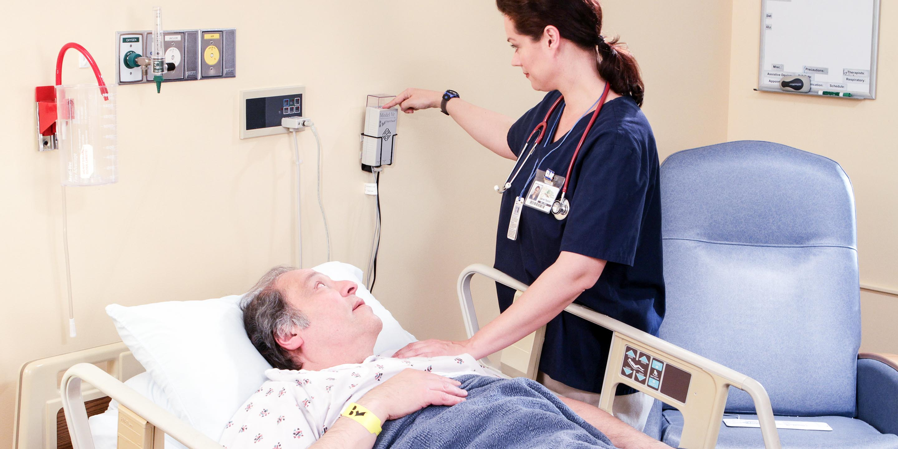 Nurse attends to Bed-Check monitor of patient