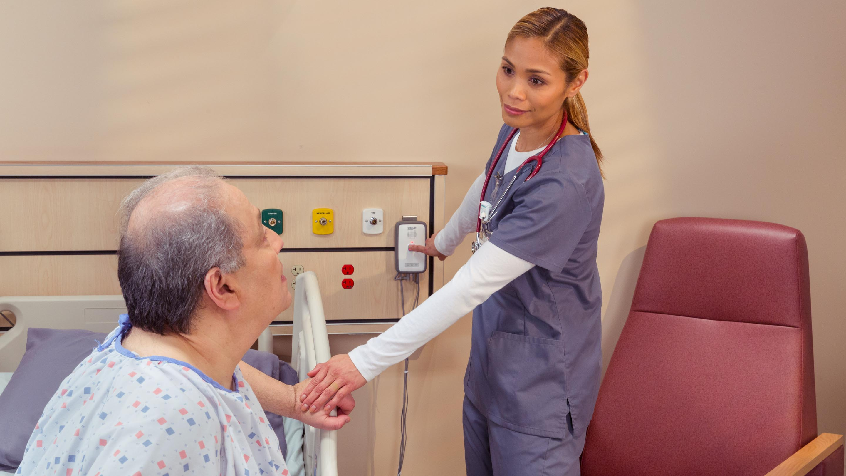 Nurse helps patient with M200 fall management monitor