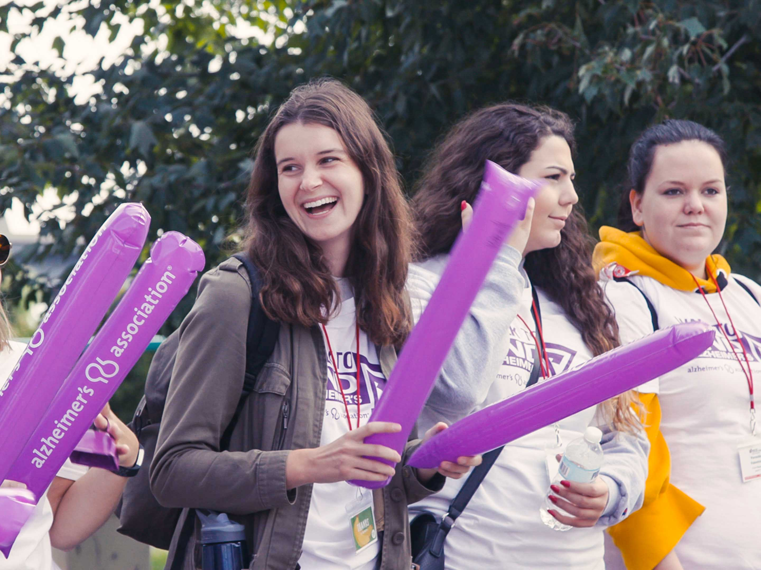 Woman waves purple tubes at Walk to End Alzheimer's