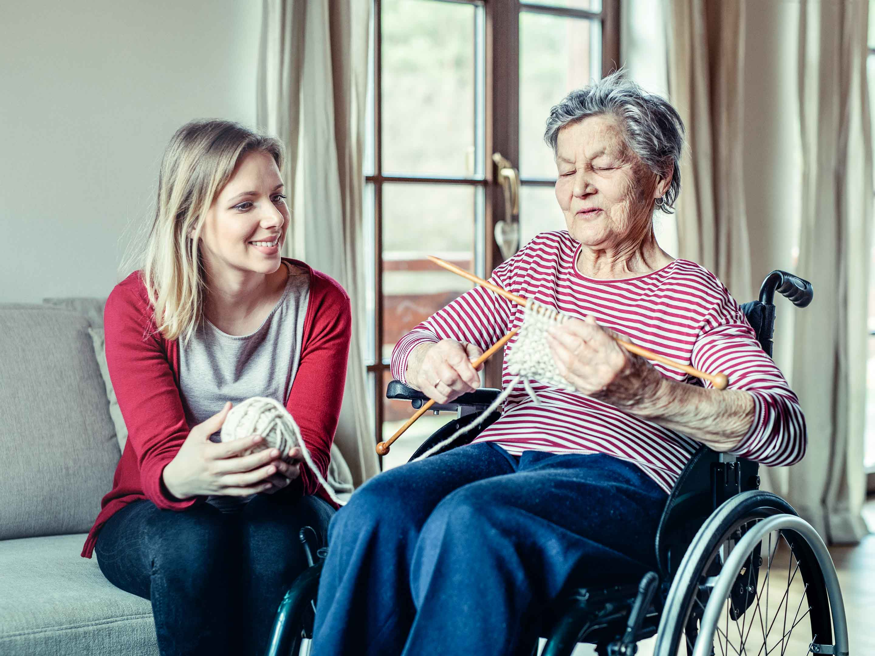 Woman sits with knitting senior living resident in wheelchair