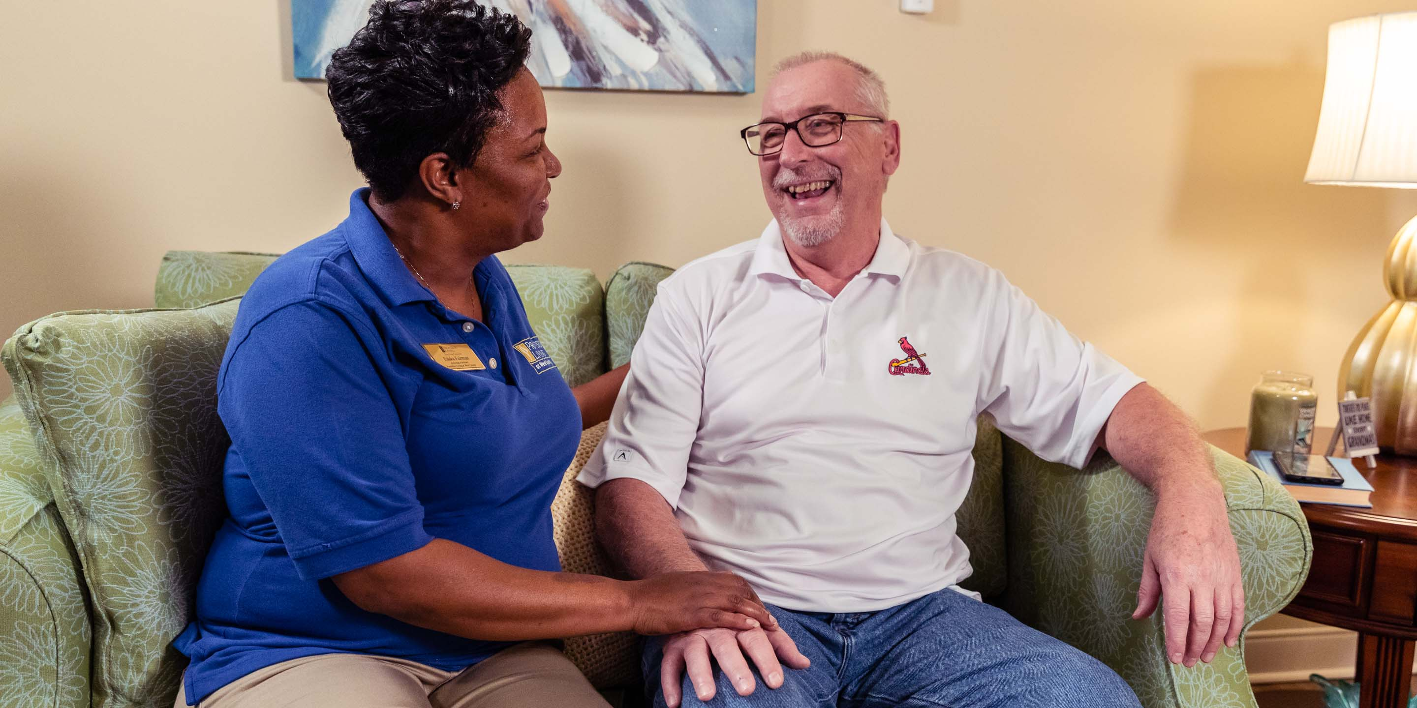 Senior living caregiver sits with laughing resident