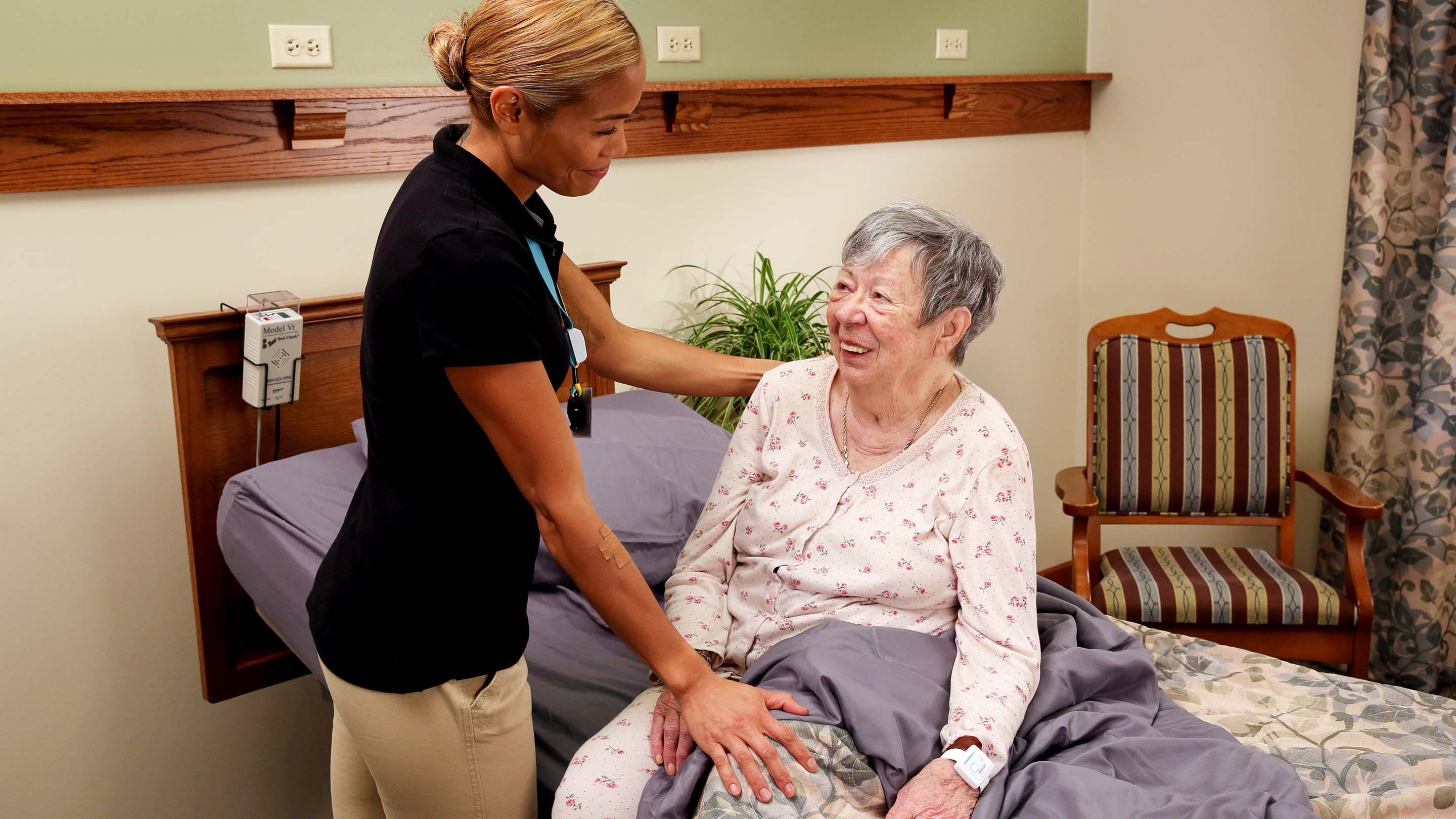 Senior living caregiver helps resident out of bed