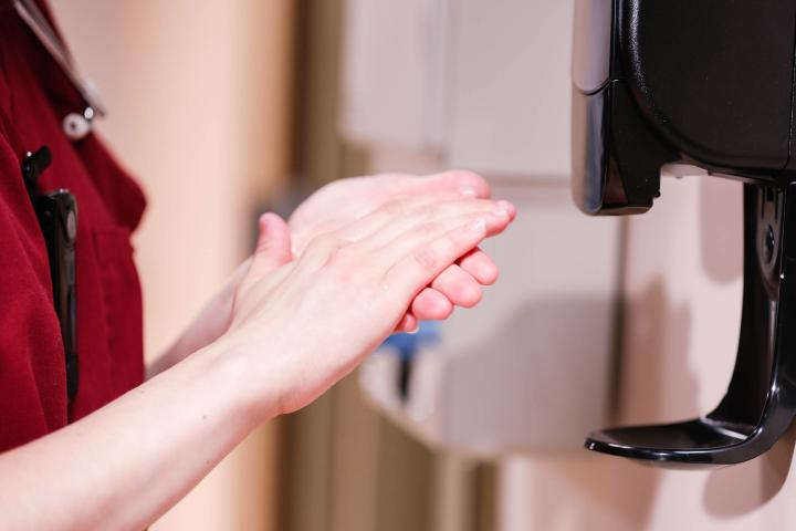 Nurse uses hand hygiene compliance station to sanitize