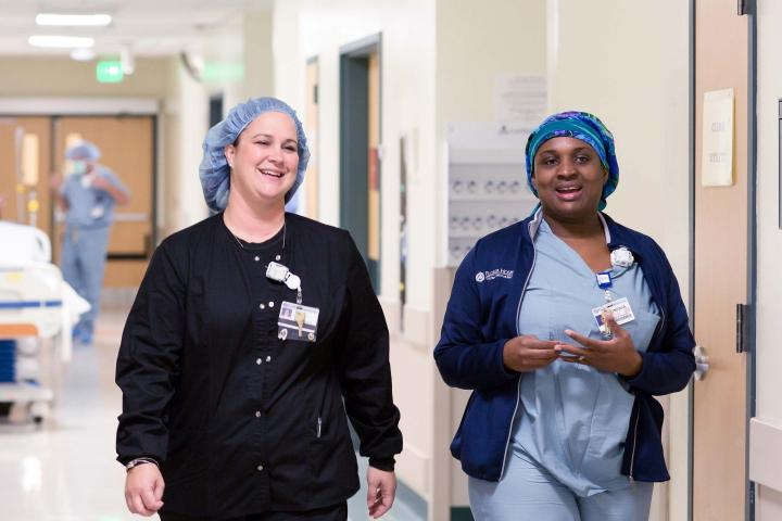 Smiling nurses walk down hospital hallway